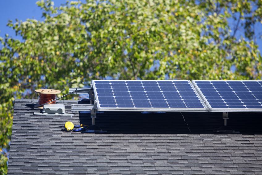 Installation of residential solar panels on the roof of a suburban home.