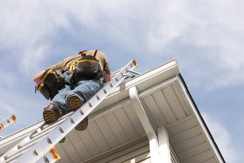 A handyman repairs his rain gutters. He is up a ladder, photo taken from ground looking up, low angle view. He wears a tool belt, sky and clouds, good copy space.